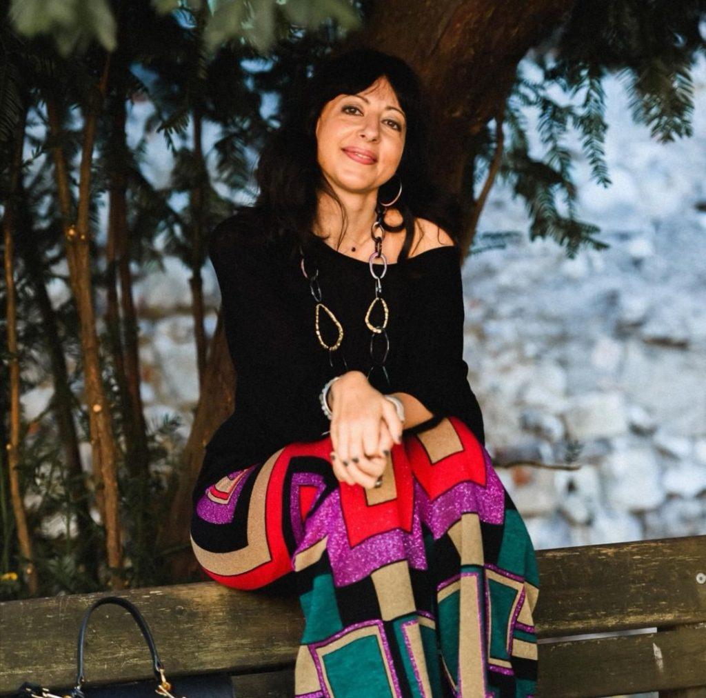Isabella The Fashion Cherry Diary indossa un paio di pantaloni con fantasia geometrica e una maglia nera