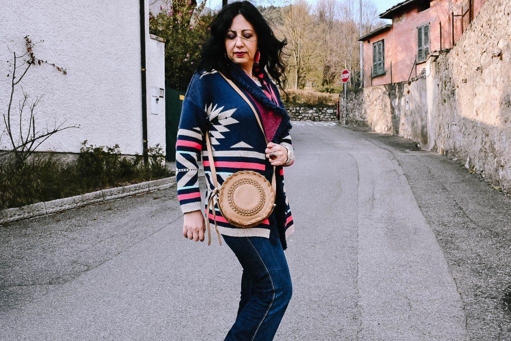 Isabella The Fashion Cherry Diary indossa un cardigan etnico con frange, una maglia a righe e un paio di jeans flare. L'outfit è corredato da una borsa tonda in cuoio