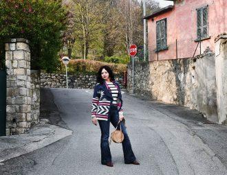 Isabella The Fashion Cherry Diary indossa un cardigan etnico con frange, una maglia a righe e un paio di jeans flare